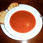 A bowl of tomato soup with toast